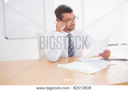 Focused businessman reading document at his desk in his office
