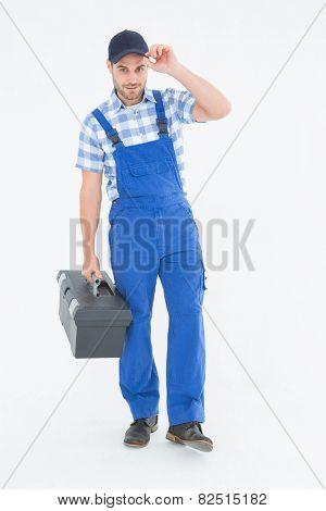 Full length portrait of confident male handyman carrying toolbox on white background