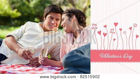 Man smiling as he looks at his friend during a picnic against valentines graphic