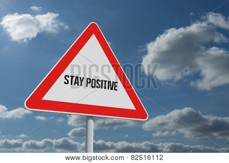 The word stay positive and hazard triangle against sky and clouds