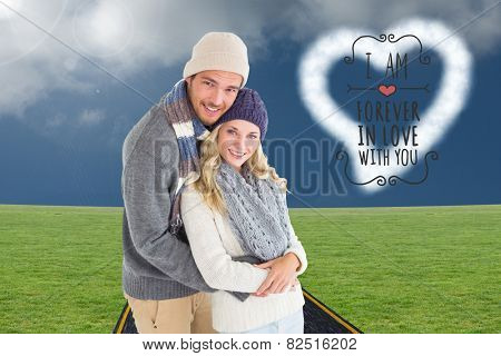Attractive couple in winter fashion hugging against road on grass