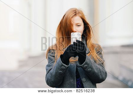 Young beautiful redhead woman in blue dress and grey coat doing selfie photo at winter o
