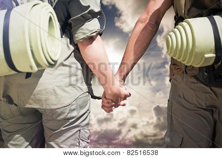 Hitch hiking couple standing holding hands on the road against dark sky with white clouds