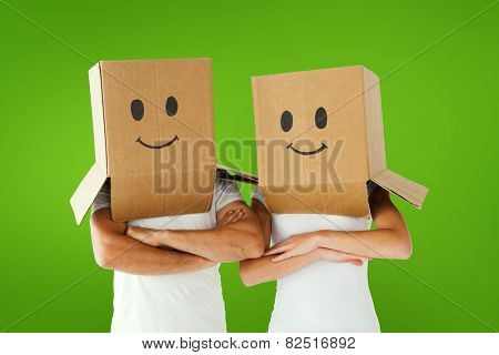Couple wearing smiley face boxes on their heads against green vignette