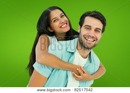 Happy casual man giving pretty girlfriend piggy back against green vignette