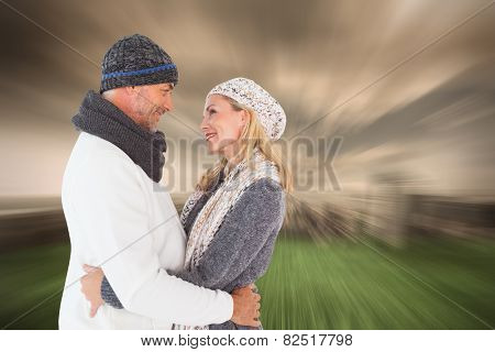 Happy couple in winter fashion embracing against stormy sky over city