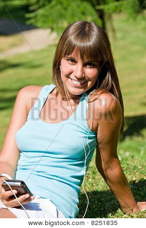 Young Woman Listen To Music In Park