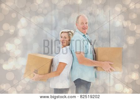 Happy older couple holding moving boxes against light glowing dots design pattern