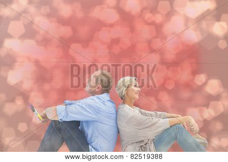 Happy mature couple holding paintbrushes against light glowing dots design pattern