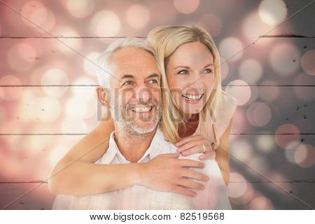 Happy man giving his partner a piggy back against light circles on black background