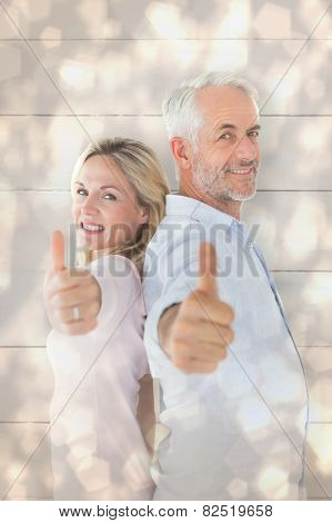 Smiling couple showing thumbs up together against light glowing dots design pattern