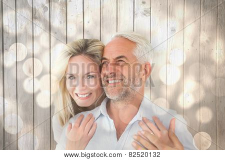 Smiling couple embracing with woman looking at camera against light circles on bright background