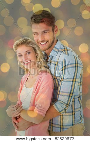 Attractive couple embracing and smiling at camera against close up of christmas lights
