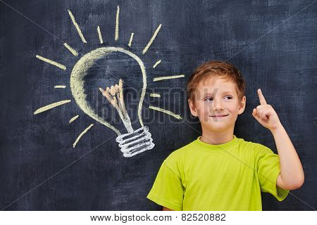 Handsome ginger schoolboy standing in front of a blackboard