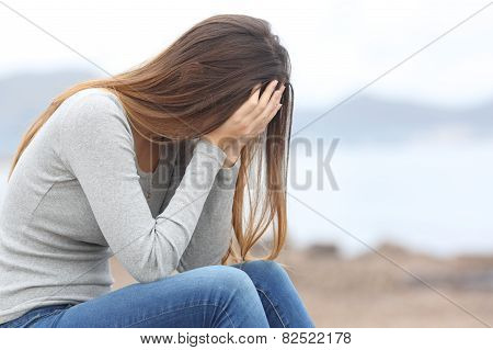Worried Teenager Woman On The Beach In Winter