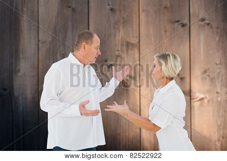 Angry older couple arguing with each other against wooden background