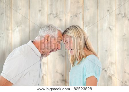 Unhappy couple having an argument against pale wooden planks