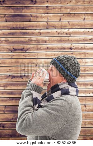 Sick mature man blowing his nose against wooden planks background
