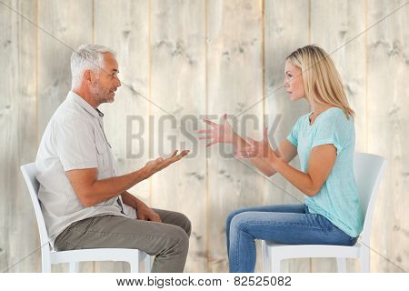Unhappy couple sitting on chairs having an argument against pale wooden planks