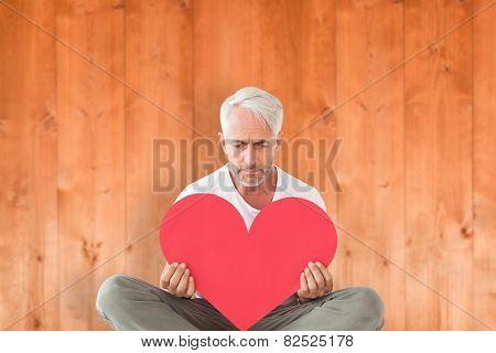 Upset man sitting holding heart shape against wooden planks