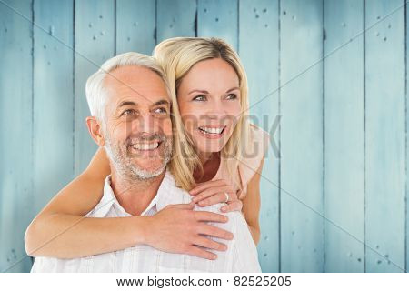 Happy man giving his partner a piggy back against wooden planks