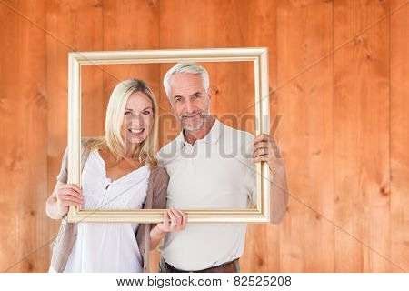 Happy couple holding a picture frame against wooden planks