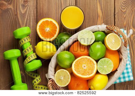 Citrus fruits in basket and dumbells. Oranges, limes and lemons. Over wood table background