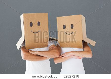 Couple wearing smiley face boxes on their heads against grey