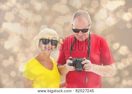Happy mature couple wearing sunglasses against light glowing dots design pattern