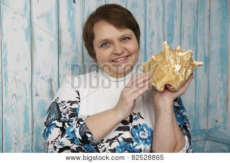 Old woman holding a seashell. Selective focus on her face. Blue marine background. Woman in her sixt