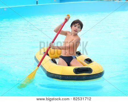 Preteen Little Boy In Aqua Park Swim On Rubber Boat With Oar