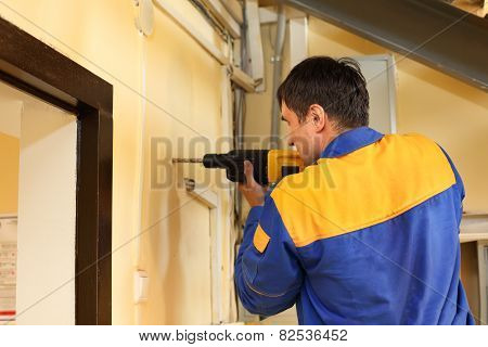 male with electric drill making hole in wall