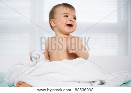 Happy baby sitting in a towel after bathe