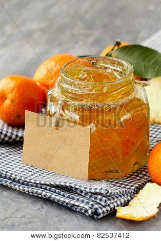 orange (tangerine) jam in a glass jar on the table
