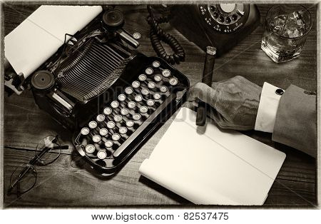 Closeup of a writer at his desk with a typewriter, rotary telephone, glass of whiskey and a cigar. Black and white toned image for a vintage feel. Only the mans hand holding a cigar is shown.