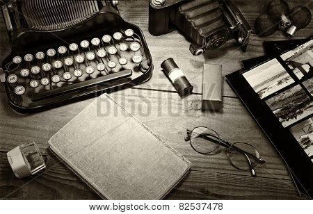 Closeup of a vintage photography still life with typewriter, folding camera, loupe, roll film, flash bulbs, contact prints and book on a wood table. Black and white toned image for a vintage feel.