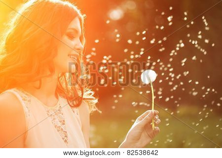 Young spring fashion woman blowing dandelion in spring garden. Springtime. Trendy girl at sunset in spring landscape background. Allergic to pollen of flowers. Spring allergy