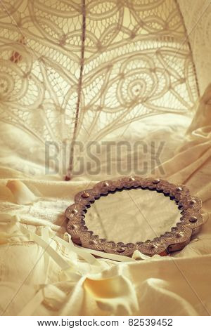 Antique mirror lying on a wedding dress with brides parasol