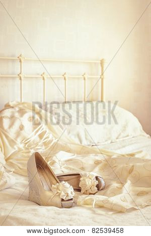 Brides wedding shoes and dress lying on the bed