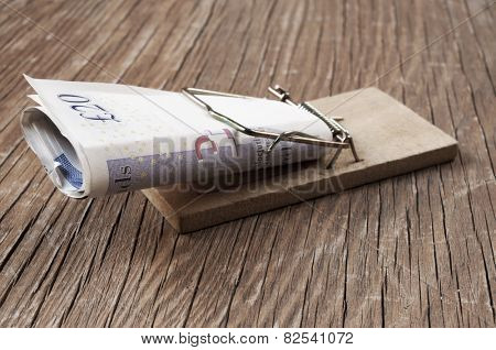 pound sterling bills in a mousetrap on a rustic wooden surface