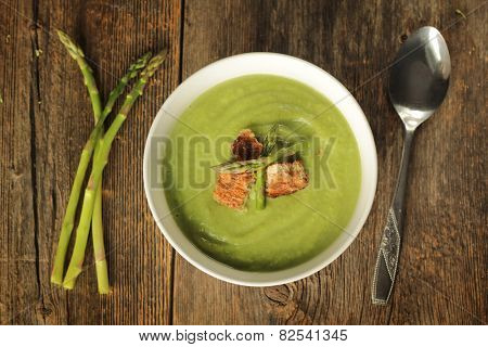 Top view of a asparagus soup in a white bowl on a rustic background