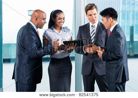 Business team of Indian, Chinese and Caucasian ethnicity discussing in front of city skyline