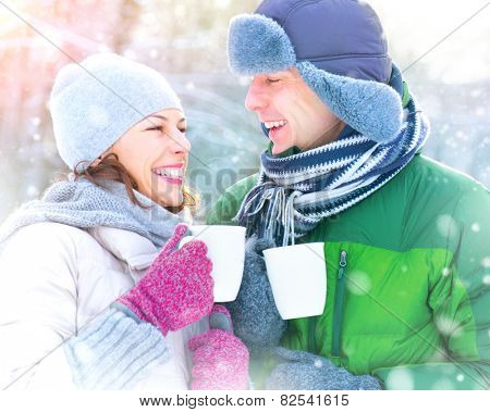 Happy Winter Couple drinking hot beverage outdoors. Having Fun in winter park. Snow. Winter Vacation. Hot Drink Outdoor. Joyful family. St. Valentine's Day celebration