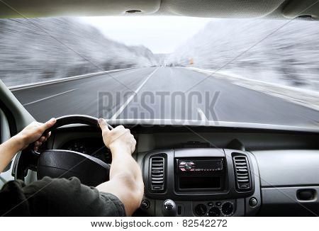Man's hands of a driver on steering wheel of a minivan car on asphalt road