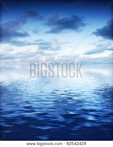 Ocean with calm waves background with dramatic sky. Blue, cold tint.