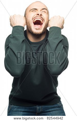 Portrait of happy excited young man screaming with arms extended . Over white background