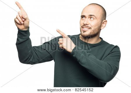 Happy young man pointing up  and looking away. Isolated on white background.