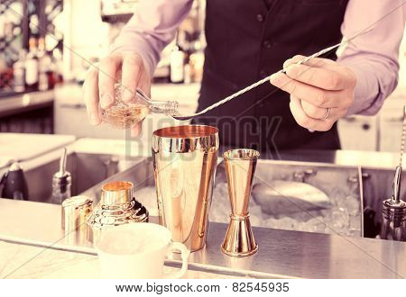 Bartender is adding ingredient in shaker at bar counter, toned image