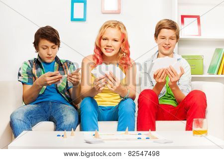Three teenagers playing table game on white sofa