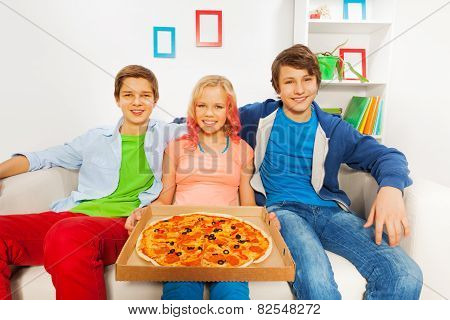 Girl holding pizza on carton and boys sitting near